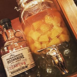 Pineapple chunks go for a dip in Monadnock Moonshine. This infusion is a key ingredient in the Pineapple Sunshine cocktail.