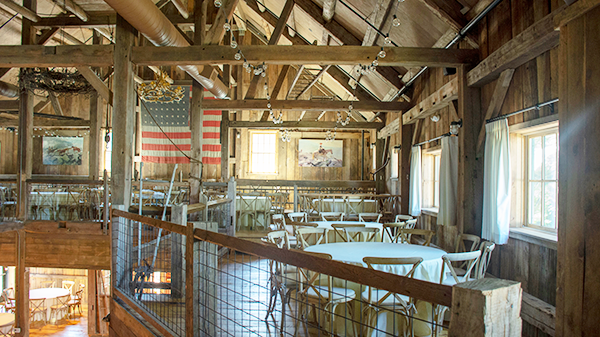 Guests will find the rustic charm continues on the second floor of The Barn with artwork, chandeliers, and seating.