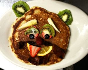 A pancake decorated to look like a face with cut fruit, from STREET.