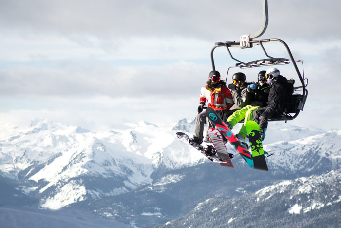 Snowboarders on a lift up a mountain.